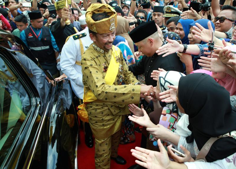 Brunei's Sultan Hassanal Bolkiah greets well-wishers who have lined the streets during a street procession to mark his Golden Jubilee in Bandar Seri Begawan on Thursday. (Brunei Prime Minister's Office/EPA-EFE photo)