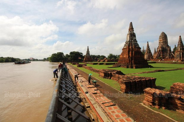 Workers reinforce flood walls at the Wat Chai Watthanaram complex on the banks of the Chao Phraya at Ayutthaya. Rising water has already harmed some riverside temples in the province. (Photo by Sunthorn Pongpao)