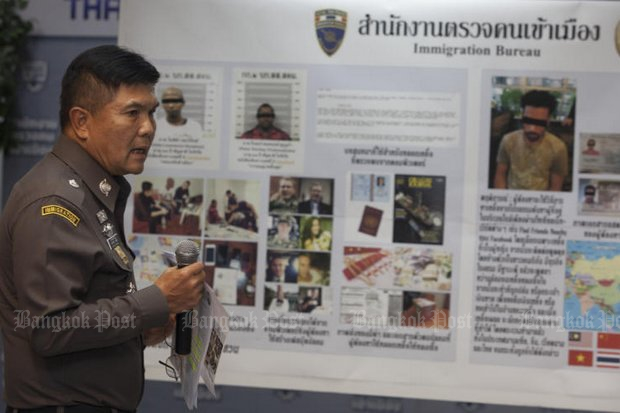 Pol Lt Gen Suthipong Wongpin, acting Immigration Bureau chief, shows a police suspects' board of an Indian and two Nigerian men detained for involvement in an online romance scam based in Bangkok. (Photo by Pawat Laopaisarntaksin)
