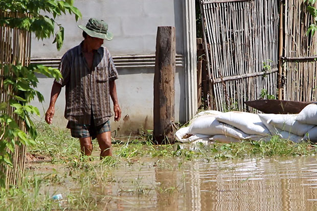 A man wades through floodwater in Kalasin on Sunday. (Photo by Yongyuth Puphuangphet)
