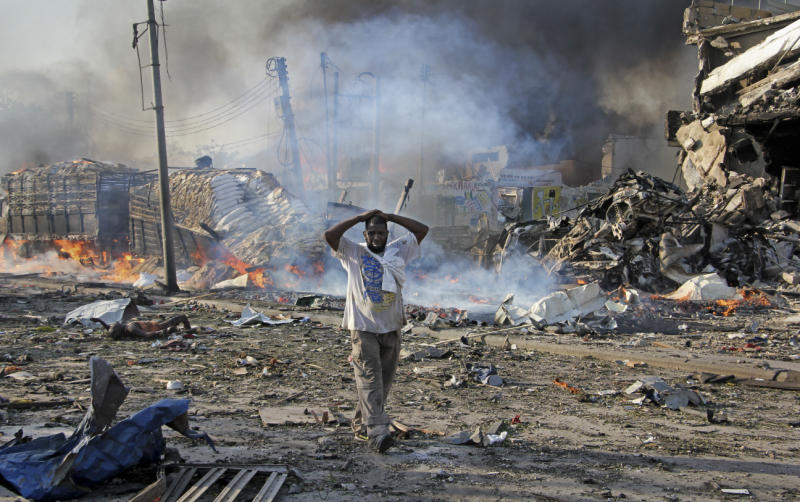 A Somali gestures as he walks past a dead body, and destroyed buildings at the scene of a blast in the capital Mogadishu on Saturday. (AP photo)