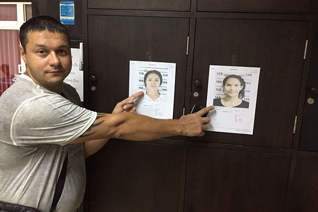 A Russian tourist identifies the robbers from their photos at the police station in Pattaya. (Photo by Chaiyot Pupattanapong)