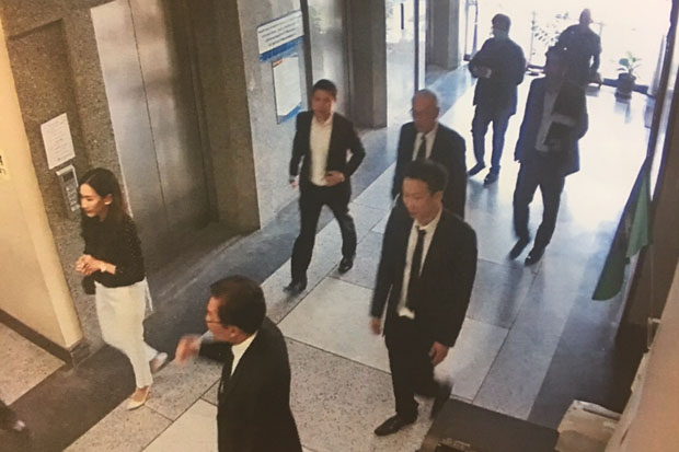 Panthongtae Shinawatra, fourth from left, arrives at the Department of Special Investigation in Bangkok on Tuesday to answer money-laundering charges. (Photo captured from DSI's surveillance camera footage)