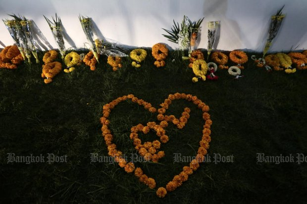 Flowers placed by mourners lie in front of a wall of the Grand Palace early this month to bid farewell to the late King Bhumibol Adulyadej, King Rama IX. Some flowers were shaped as a heart surrounding the number 9. (Photo by Patipat Janthong)