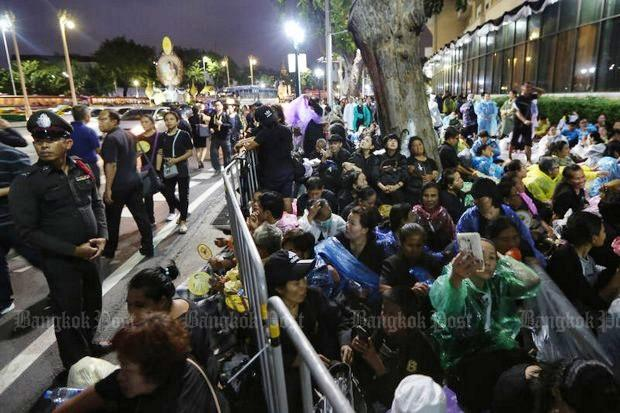 People camped overnight in the rain at the front of the Royal Hotel, one of the screening points for entry to watch the royal cremation ceremony at Sanam Luang. The screening points opened Wednesday at 5am. (Photo by Wichan Charoenkiatpakul)