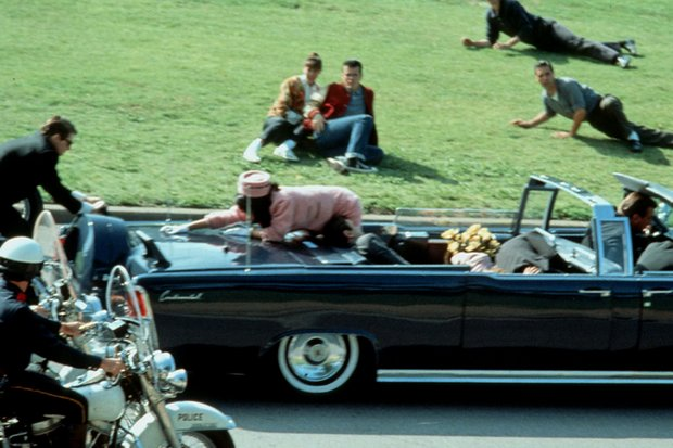 President John Kennedy slumps against his wife Jacqueline as she reaches towards Secret Service agent Clint Hill. (File photo)