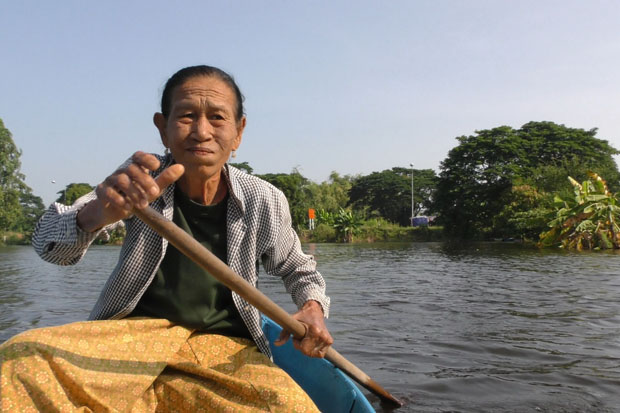 A local resident travels by boat in Sapphaya district of in Nakhon Sawan where floodwater from the Chao Phraya River has remained for a month and gives off a strong smell. (Photo by Chudate Seehawong)