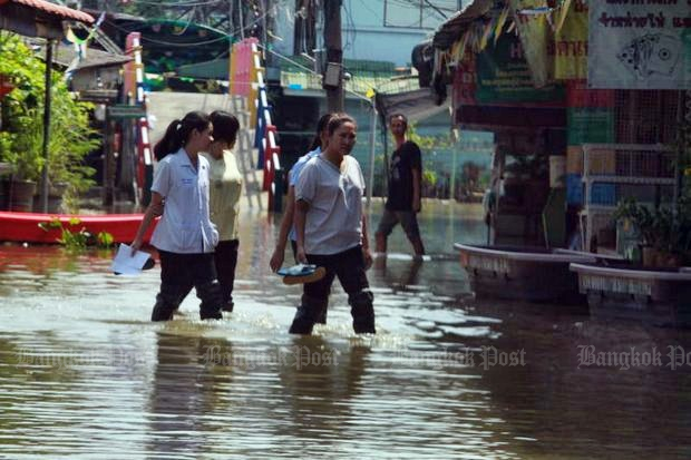 His Majesty King Maha Vajiralongkorn Bodindradebayavarangkun has ordered better rescue and rehabilitation efforts for flood victims such as these women wading through a flooded street in Sam Khok district of Pathum Thani. (Photo by Somchai Poomlard)