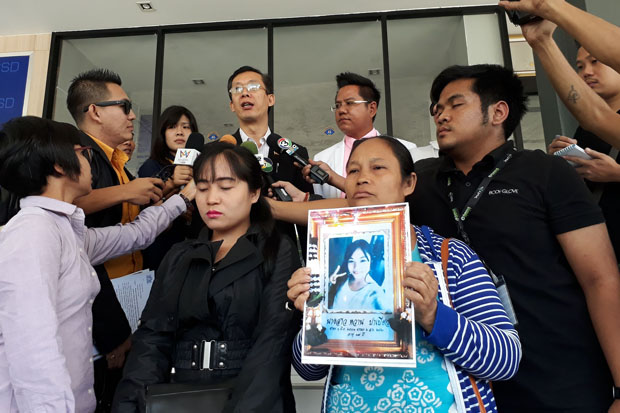 The family of the dead Myanmar womanshows her photo while an official of the Myanmar embassy speaks to reporters on the suspicious death at the Crime Suppression Division in Bangkok on Tuesday. (Police photo)