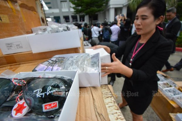 A DSI raider inspects boxes of luxury, brand-name goods including 210,000 pairs of counterfeit glasses carrying labels of Ray-Ban, Prada, Dior, Louis Vuitton, Chanel, Burberry and Oakley. (Photos by Supakit Buyam)