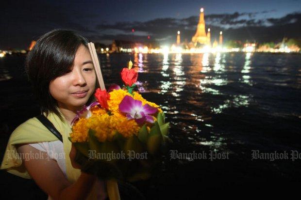 A Bangkok woman prepares to float her krathong at the Chao Phraya River bank during last year's festival. (Bangkok Post file photo)