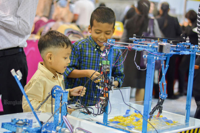 Children enjoy playing with robotic hands to pick up objects during the EDUCA 2017 Fair at Impact Arena Hall at Muang Thong Thani Exhibit and Convention Centre near Bangkok in October. (Photo by Supakit Buyam)