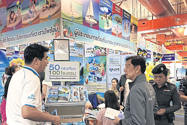 A travel agency answers questions at a tourism fair.