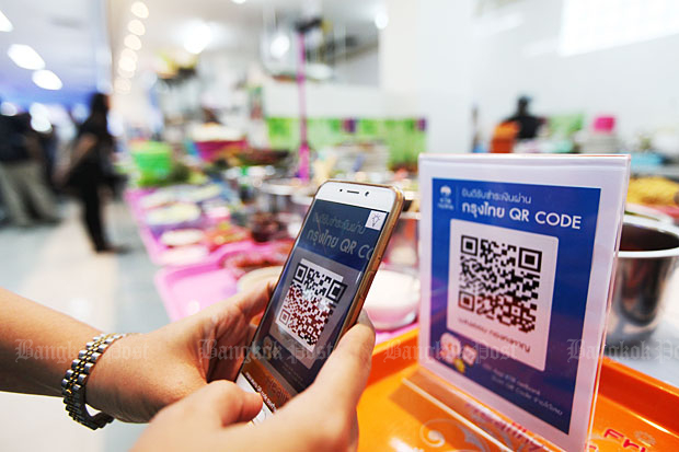 A customer tries out the Krungthai Bank QR code payment system being tested in the food court at the Finance Ministry headquarters and other locations nearby in Bangkok. Photo: Thiti Wannamontha
