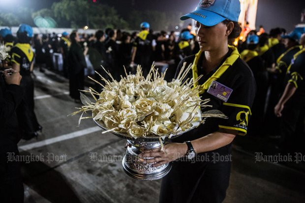 A volunteer holds <i>dok mai chan</i> used to mark the royal cremation ceremony. Two provincial governors have been transferred and denied new posts for shaming the ceremony. (Bangkok Post file photo)