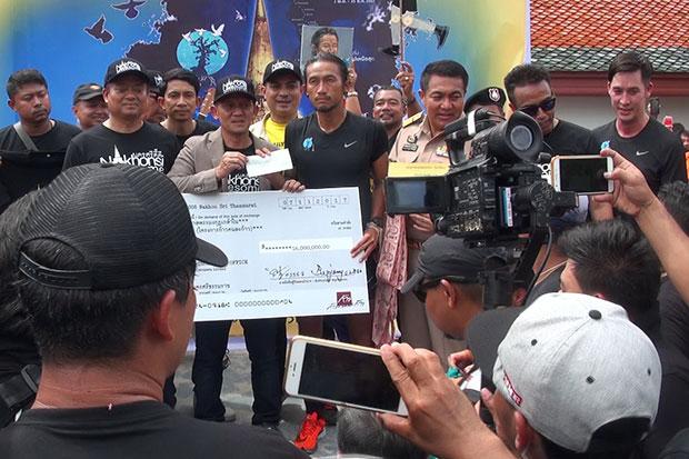 Toon Bodyslam, or Artiwara Kongmalai, receives a cheque for 16 million baht donated by Nakhon Si Thammarat businessman Jimmy Chawala, at Wat Phra Mahathat Maha Vihara in Muang district on Sunday. (Photo by Nujaree Raekrun)