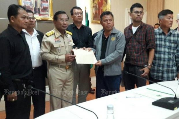 Agriculture and and Cooperatives Minister Chatchai Sarikulya (in khaki uniform) accepts petition from rubber growers. (Post Today photo)
