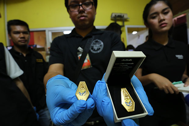 An official shows some of the royal cremation commemorative pins, suspected to be  illegally produced, seized at the  Chayatham Co factory in Bangkok's Lat Phrao district on Friday morning. (Supplied photo)