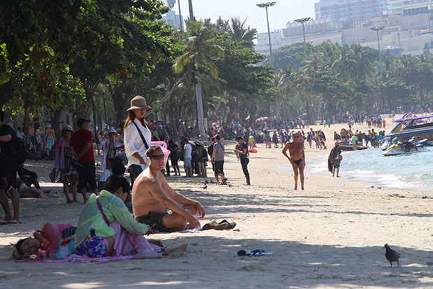 Tourists sit on a Pattaya beach that will be without umbrellas or chairs for the next three days. (Photo by Chaiyot Pupattanapong)
