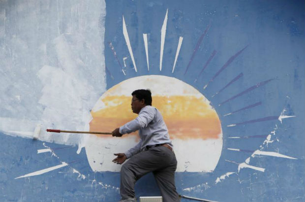 A Cambodian worker paints over the opposition Cambodia National Rescue Party's logo at its headquarters in Phnom Penh, Cambodia, on Saturday. (EPA photo)