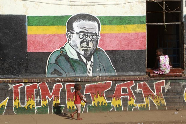Children play near a painting of Zimbabwean President Robert Mugabe in Harare on Monday. (AP photo)