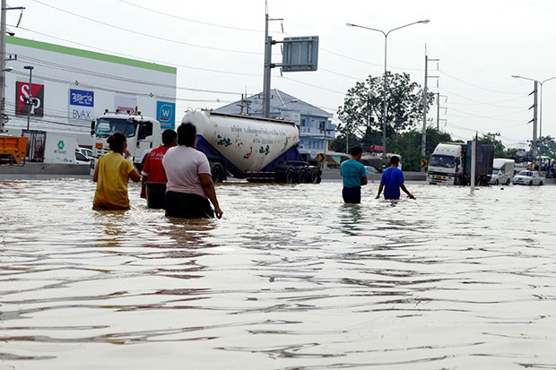 Residents of Phetchaburi's Muang district wade through thigh-deep floodwater outside the Big C store on Phetkasem Road on Thursday. (Photo by Chaiwat Satyaem)