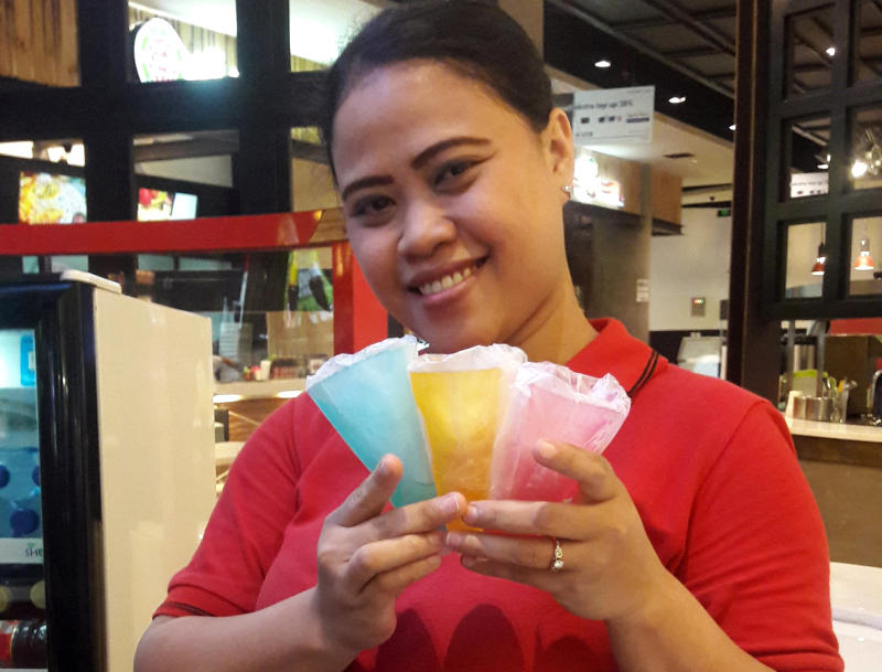 An ice cream parlor attendant holds cones made of seaweed jelly called Ellojello, a product of seaweed-based plastic ware company Evoware, at a shopping mall in Jakarta. (Reuters photo)