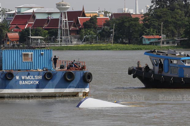 A wind turbine tower on the sunken barge barely shows above water, in the Chao Phraya River, Pathum Thani, on Tuesday morning. (Photo by Wichan Charoenkiatpakul)