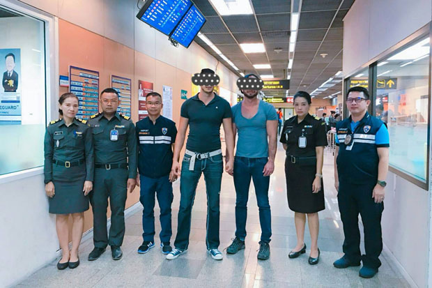 Immigration police arrested two Americans at Don Mueang airport and said they confessed to posing for photos at the Temple of Dawn while showing their naked buttocks. (Immigration police photo)