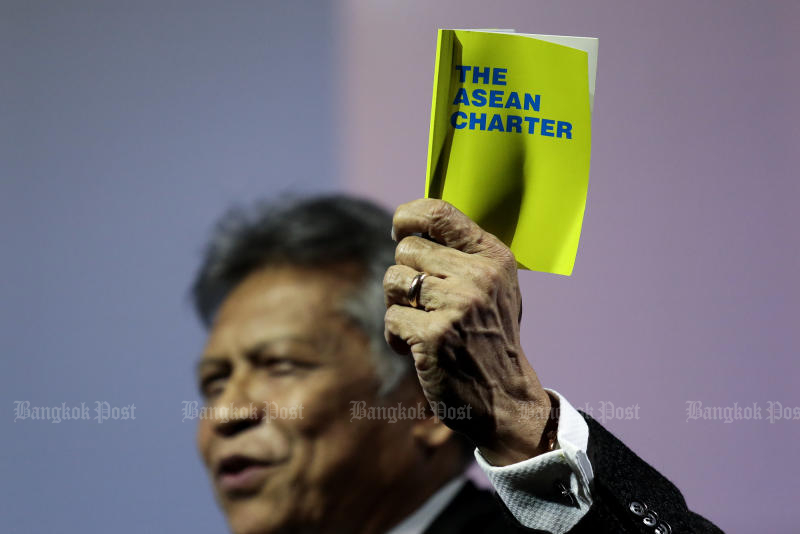 Surin Pitsuwan raises the Asean charter during his speech on the 50th year of the organisation at the Bangkok Post Forum on Nov 16, 2017. (Photo by Patipat Janthong)
