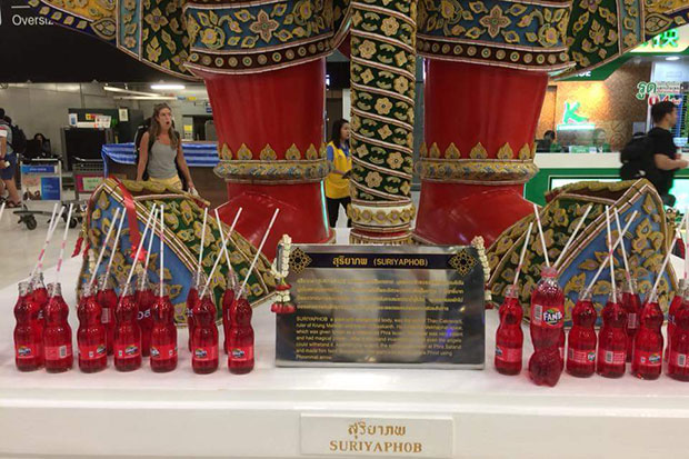 About two dozens of the bottles of red soda drinks are seen at the feet of Suriyaphob, one of the ogres standing at Suvarnabhumi airport. (Photo from @Phil_Prajya Twitter account)