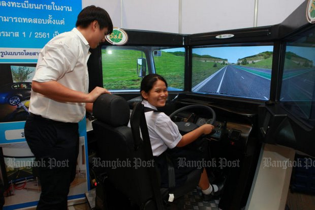 A student tries out a vehicle simulator at the 13th Thailand Road Safety Seminar titled 'Invest for Sustainable Road Safety'. The government is investing in road safety. (Photo by Somchai Poomlard)