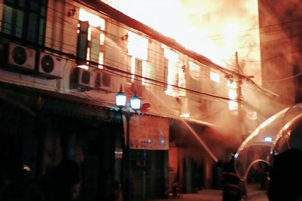 Firefighters battle to control the blaze that spread quickly through 13 old buildings in historical Phraeng Nara area of Bangkok's Phra Nakhon district. (Photo: JS 100)