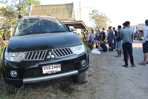 The covered body of the dead schoolgirl lies on the road after it was retrieved from a roadside canal. The black Mitsubishi crashed into the rear of the pickup taking her and two other students to school, catapulting them from the vehicle. (Photo by Saichon Srinuanchan)