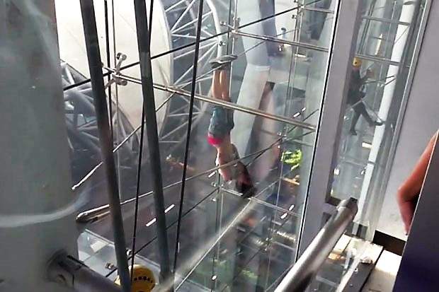 The foreign woman hangs by her feet from an exterior cable at Suvarnabhumi airport terminal on Wednesday morning. She later dropped safely onto an airbag.(Photo by Sutthiwit Chayutworakan)