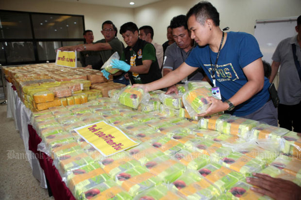 Police arrange packs of methamphetamine allegedly seized from two suspects in a raid in Nonthaburi province at the Royal Thai Police Office in Bangkok on Thursday. (Photo by Apichart Jinakul)