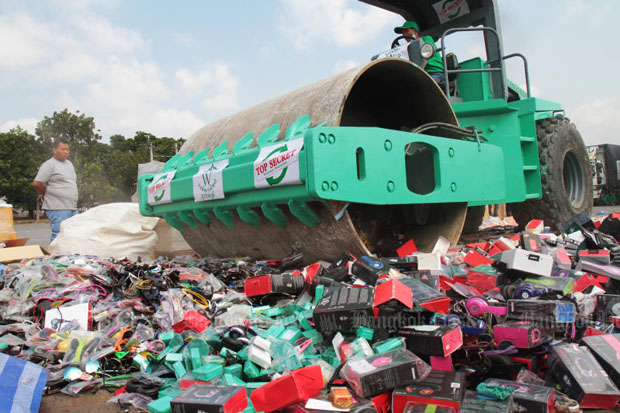 A road roller crushes 300 tonnes of pirated electrical goods, luxury products and other items worth 141 million baht at an event staged in March this year at an army base in Bangkok. (Post file photo by Tawatchai Kemgumnerd)