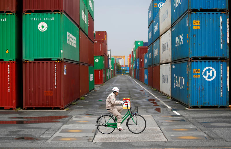 A worker rides a bicycle in a container area at a port in Tokyo on April 21, 2014. (Reuters file photo)
