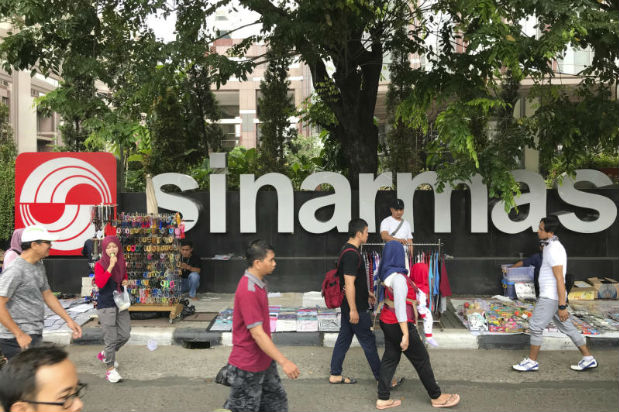 In this Oct 1, 2017 photo, people walk past Sinarmas Land Plaza during a car-free day at the main business district in Jakarta, Indonesia. Despite its denials, Sinarmas, one of the world's biggest paper producers, has extensive behind-the-scenes ties and significant influence over wood suppliers linked to fires and deforestation that have degraded Indonesia's stunning natural environment. (AP Photo)