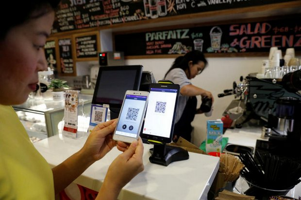 Operations manager Frances Sy shows a method to pay for coffee with an instant transfer via QR code at the new Ducatus cafe in Singapore. (Reuters photo)