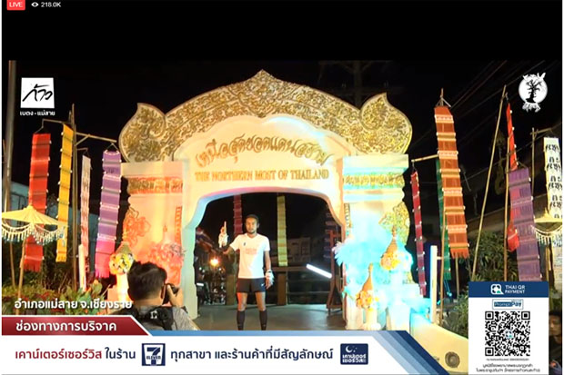 Artiwara 'Toon Bodyslam' Kongmalai, 38, poses with the northernmost arch in Mae Sai district, Chiang Rai, when he finished his South-North charity run Monday evening. (Picture captured from the charity run project's live Facebook coverage)