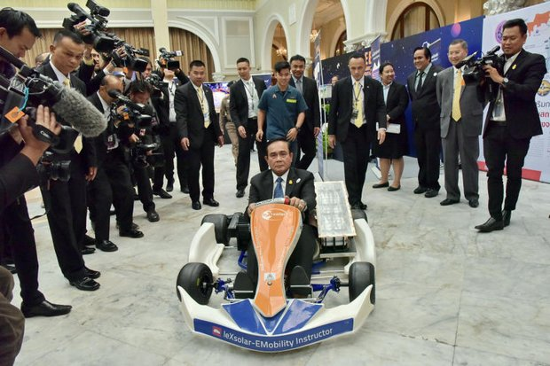Prime Minister Prayut Chan-o-cha rides an electric go-cart, an innovation produced by a local vocational college in Sukhothai province where ministers held a mobile cabinet meeting Tuesday. (Reuters photo)