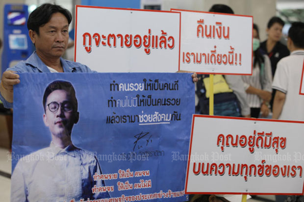 File photo - Victims of convicted Ponzi scheme fraudster Phudit Kittitradilok (whose picture is in poster) show up at the Department of Special Investigation in Bangkok in May to seek its legal action against him. The Criminal Court sentenced him to 13,275 years in jail for the fraud and money-laundering on Friday. (Photo by Apichit Jinakul)
