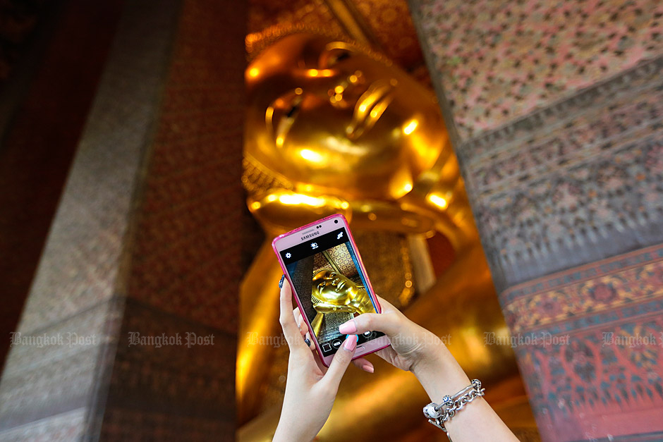 Picture perfect: A tourist takes a picture of one of the many golden statues in the temple. Photo: Patipat Janthong
