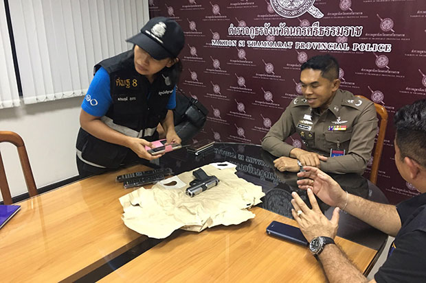 Nakhon Si Thammarat police chief Pol Maj Gen Wanchai Ekpornpitch (centre) displays the pistol allegedly fired by rocker Sek Loso in front of the statue of King Taksin the Great in Phrommakhiri district in the southern province on Friday. (Photo by Nujaree Raekrun)