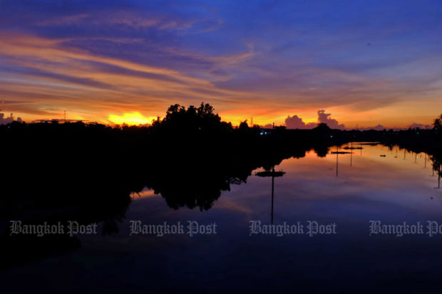 The last golden streak of sunset transforms the skyline above a canal in Bang Bua Thong, Nonthaburi. The district is located about 25km northwest of central Bangkok. Photo: Chanat Katanyu)