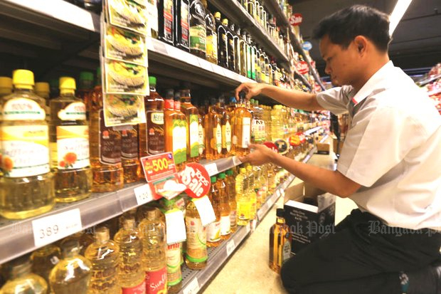 A supermarket clerk stocks the cooking oil shelf with palm oil. (Photo by Jiraporn Kuhakan)