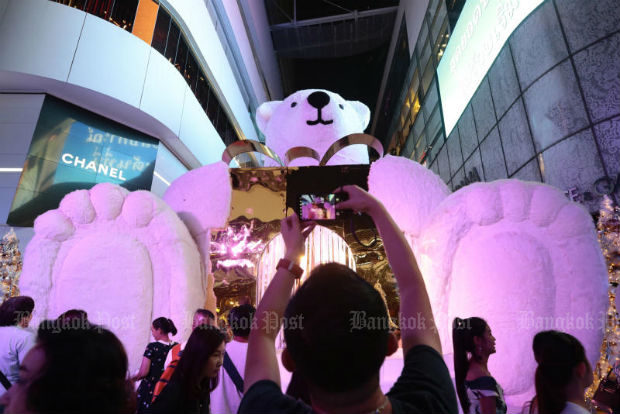 A man takes a picture of a giant polar bear display at the EmQuartier shopping mall packed with Christmas and New Year revellers in November 2017. (Photo by Patipat Janthong)