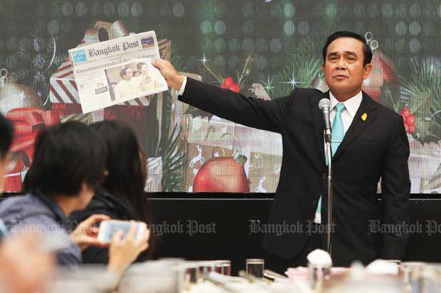 Prime Minister Prayut Chan-o-cha brandishes Wednesday's Bangkok Post at a special lunch he threw for the press as he insists for the second time in a week that he and the junta have always given the press the freedom to report. (Photo by Thiti Wannamontha)