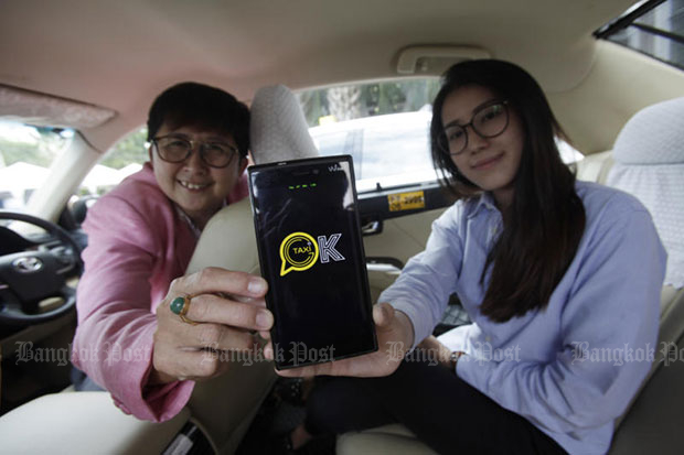 The logo of Taxi OK is seen on a mobile phone. (Photo by Pornprom Satrabhaya)